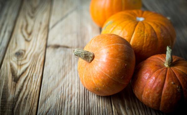 Some pumpkins in basket on wood background