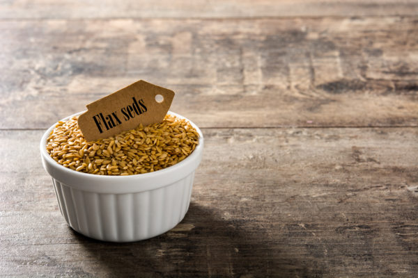 Golden flax seeds in white bowl